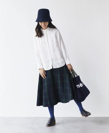 白シャツ&チェックのスカートというトラッドなコーデ。明るめブルーのタイツで遊び心を出します。