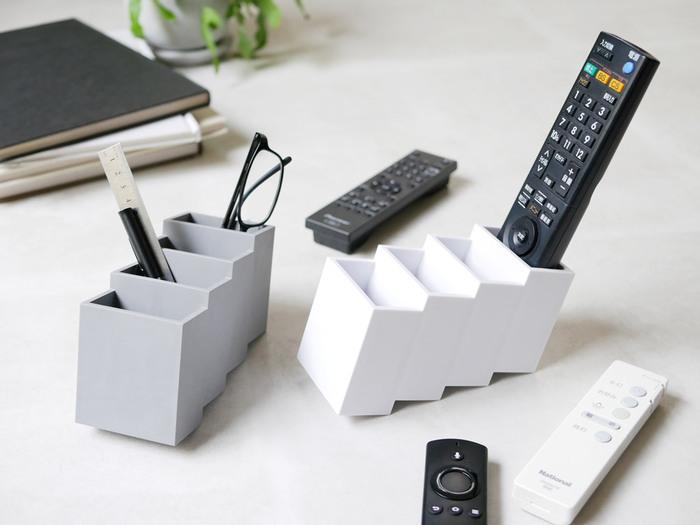 階段のようなデザインがユニークなリモコンスタンド。リモコンがきれいに収まり、出し入れしやすいよう設計されています。ペンやメガネも一緒に収納できて便利ですね。