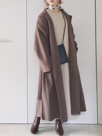 白のロングワンピースに、ブラウンのロングコートとブーツを合わせたフェミニンなコーディネートです。黒のショルダーバッグをアクセントにプラスして、首元にはベージュ×黒で色味を合わせたドット柄スカーフをアクセサリー感覚でオン。