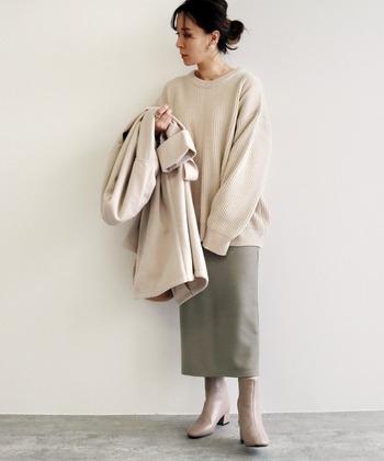 バックスリットの入ったリブタイトスカートに、ベージュのニットを合わせたフェミニンなコーディネート。アウターやブーツもベージュ系のカラーで揃えて、カーキのタイトスカートをメインに据えたスタイリングに仕上げています。