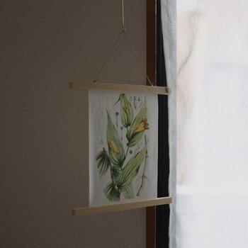 ポスターフレームをフックなどで吊るせば壁から離れた空間にも飾ることができます。ゆらゆらと動きが出せるのも面白いですね。