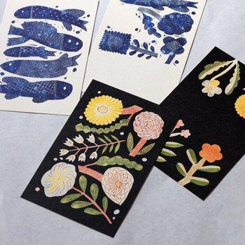 陶芸作家の鹿児島睦さんの作品に用いられている図案をグラフィックにしたポストカード。 色も形もシンプルにデフォルメされたお魚とお花たちにより、愛らしい雰囲気が漂います。