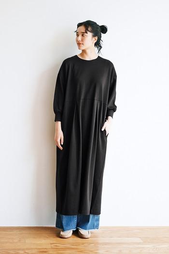 重たく見える黒のロングワンピースを軽快に見せてくれるのが、ウォッシュ加工が施されたラフなデニム。切りっぱなしの裾をワンピースからのぞかせると、コーデの程よいアクセントになりますよ。季節感をプラスしたいなら、ベージュのモカシンでほっこり感をオンするのがおすすめです。