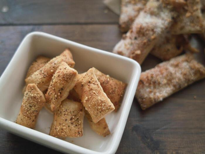 残りの切れ端の生地などで作る、ペッパーチーズパイ。2~3mmの厚さにした生地を一口サイズにカットして、粉チーズと黒胡椒を振りかけます。13~18分程度、きつね色になるまで焼けば完成!生地を伸ばしたあとに約10分、冷蔵庫で休ませるのがポイント。サックサクの食感をお楽しみください。