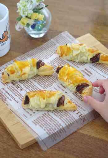 冷凍パイシートと板チョコレートを使ったお子さまでも作ることができる簡単レシピ。冷凍パイシートは三角形になるようにカットして、チョコレートをくるっと包むイメージです。オーブンで焼く前に卵黄を表面に塗っておきましょう。  カフェで食べるようなチョコクロワッサンは絶品。ホワイトチョコレートで作っても美味しいですよ。