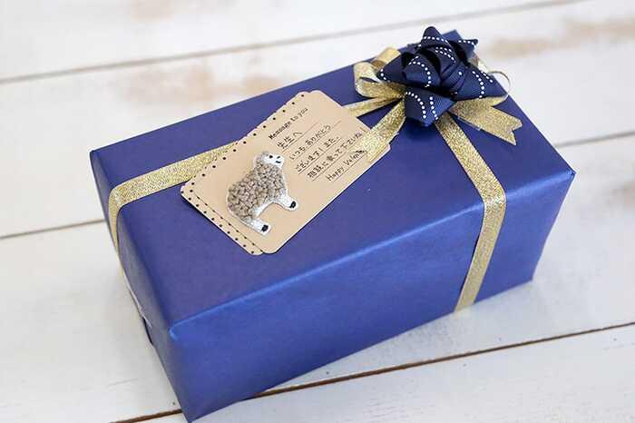 無地の包装紙で包み、リボンを十字掛けしたシンプルなラッピングは、ギフトリボンを添えることで豪華な雰囲気に仕上げられます。包装紙との色合いをあわせると統一感が出せますよ。お世話になっている人への贈り物にもおすすめです。