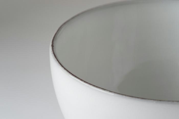 食卓にあると、琺瑯のようななめらかな白色に見えますが、手に取ってよく見ると釉薬のかかり具合により、素地が見えている部分やたまりができている部分などがあり、とくに縁の部分は素地が見えておりアクセントとして全体を引き締めています。大量生産品にはない、手仕事ならではの重厚な味わいがあります。
