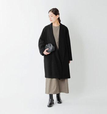 黒のロングコートに、カーキカラーのシンプルなワンピースを合わせた着こなしです。黒系のバッグやシューズで、大人っぽい印象に。コートの前を閉めるだけで、シンプルなアイテム同士のコーディネートにアクセントをプラスできます。