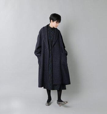 黒のワンピースに、ほんのりネイビーがかった黒のロングコートを合わせたシックなコーディネート。全身暗い色だと重くなりすぎてしまいますが、足元にシルバーのパンプスを合わせて差し色にし、軽さをプラスしています。