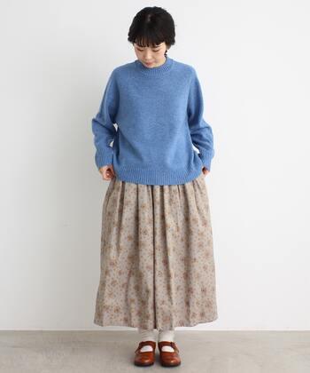 ブルーのニットトップスに、ベージュの花柄スカートを合わせたコーディネートです。足元は白靴下×ブラウンのシューズでナチュラルな印象に。キレイめカラーのトップスが、ほどよいレディ感を演出してくれます。