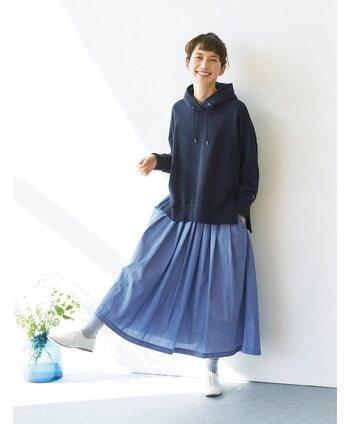 ブルーの細いストライプが入ったスカートは、ネイビーのフーディーと合わせて青コーデに。足元は白シューズで爽やかにまとめて、キレイめブルーを大人カジュアルな印象で着こなしています。