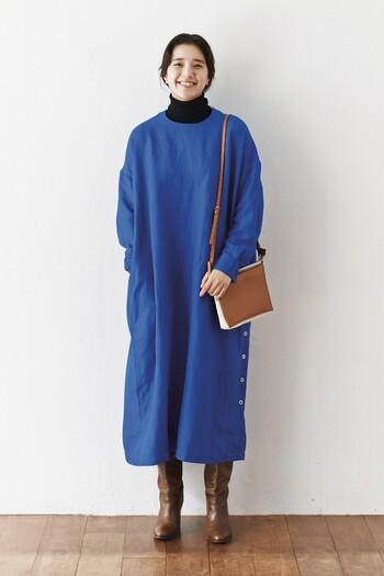 厚手のリネン素材を使ったキレイめブルーのワンピースは、一枚でもおしゃれに着こなせるアイテム。インナーに黒のタートルネックを重ねて、季節感とトレンド感を両立しています。ブーツとバッグはブラウン系で、大人っぽさを意識したコーディネートに。