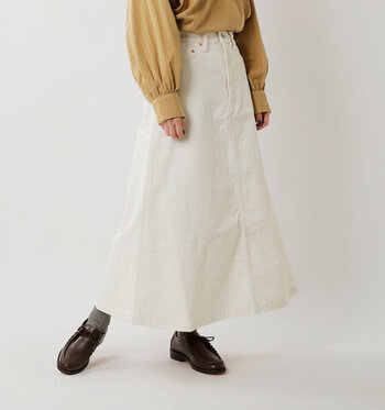 コーデュロイ素材の白ロングスカートは、フレアシルエットが女性らしい印象を与える一枚。温かみのある素材感は、ニットとの相性も抜群。キュッと締まったウエストラインなので、タックインもサマになります。