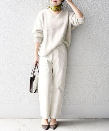 白のVネックニットに、白のベイカーパンツを合わせた着こなし。足元はグレー系のパンプスで、ホワイトコーデの差し色をプラスしています。首に巻いたスカーフもアクセントに。白ならどんな色とも相性がいいので、派手めなスカーフもさらっと合わせられますよ。