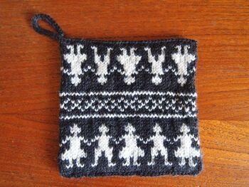 棒針の編み込み技法を使った鍋敷きです。筒状に編みながら同じ柄を2回繰り返し、それぞれを表側と裏側にしています。