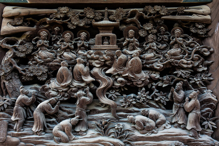 """柴又帝釈天は、別名""""彫刻の寺""""と呼ばれるほど、寺内には多くのりっぱな木彫り彫刻があることでも知られています。帝釈堂内陣の外側にある「法華経説話彫刻」は、仏教経典の中でも最も有名な「法華経」の説話を10説を選び、彫刻にしたもの。  こちらの「多宝塔出現図」は、多宝塔(多宝如来の塔)が、地面から涌き出してきて人々の信仰をほめたたえ、その塔を礼拝している人々の歓喜の様子を表しています。"""