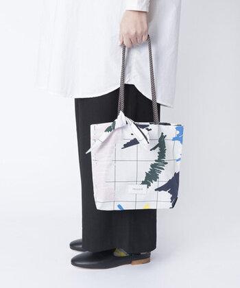 軽やかな綿素材でできたミニサイズのトートバッグ。控えめなチェック柄に、マジックで試し書きしたような柄がかわいいですね。