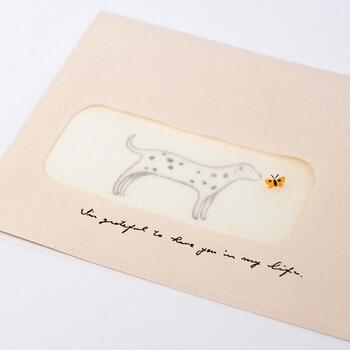 小窓付きの封筒を使い、まるで紙芝居のような楽しいストーリーを想像できる、仕掛けのある紙芝居カードの「ドック」。届いたときには、淡い色の封筒の小窓から可愛らしい犬がのぞいています。