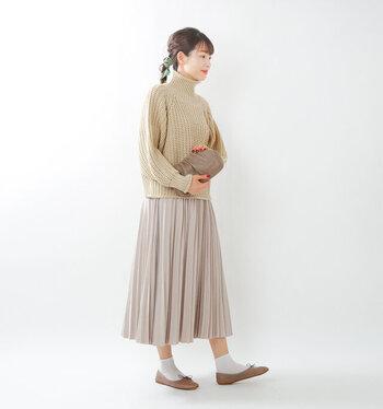 ベージュのニットトップスに、トーン違いのベージュのプリーツスカートを合わせたコーディネート。バッグやパンプスもベージュで揃えて、統一感をアピールした着こなしです。足元は白の靴下で爽やかにまとめて。冬場は黒やネイビーのアウターを羽織って、コーデを引き締めても◎