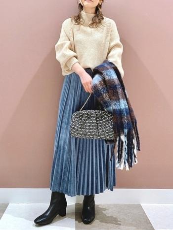 ベージュのハイネックニットに、ブルーのプリーツスカートを合わせたコーディネート。同じくブルーの入ったストールで、全身に統一感をプラスしています。足元は黒のブーツで、季節感を演出しつつ引き締めポイントとしても◎