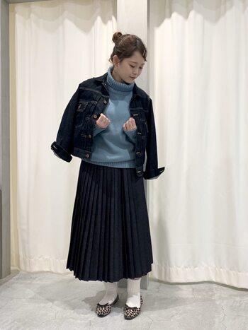 ネイビーのデニムプリーツスカートに、薄いブルーのタートルネックニットを合わせたコーディネートです。スカートと色味を合わせたデニムジャケットを羽織って、ブルーで統一した大人カジュアルなスタイリング。足元は白靴下×レオパード柄パンプスで、シックなカラーにアクセントをプラスしています。