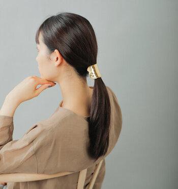 髪の毛を結んだゴムに引っ掛けるようにはめて使う、真鍮のヘアピアス。いつものひとつ結びがエレガントな印象にチェンジ。