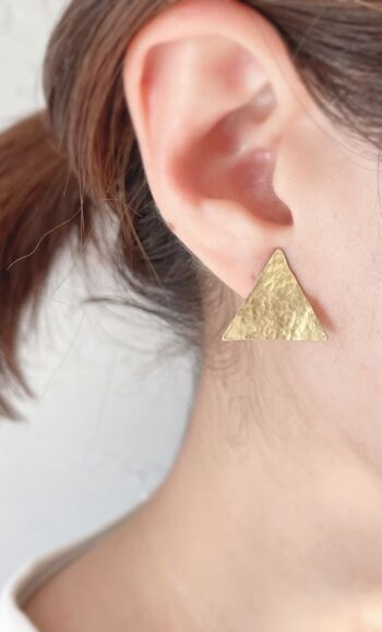 軽く叩いて独特のニュアンスを出した三角形のおしゃれなピアス。表面の凹凸が動くたびに光を反射して、耳元でゆらゆらと輝きます。