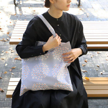 """""""PUKETTI""""柄のトートバッグは、薄いブルーをベースにした落ち着きのあるカラーリング。買い物などにもちょうどよいサイズ感で、エコバッグとして活用するのもおすすめです。"""