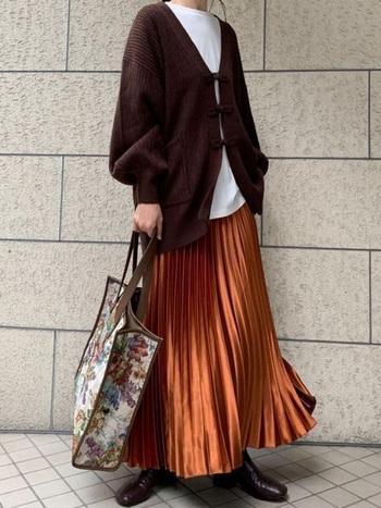 光沢のあるプリーツスカートとツヤのあるブーツ、全体的にブラウンで纏めて上質な大人の印象に。バッグはあえて柄物を選ぶところにセンスが光ります。