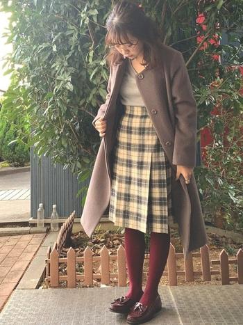 ノーカラーのコートにチェックの広がりを抑えたスカートを合わせた着こなし。自分らしいエッセンスを加えるなら、ボルドーなど暖色のカラータイツを合わせてみてはいかがでしょう?悪目立ちしませんし、コーデのポイントになります。