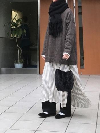 フリンジのあるマフラーは前で見せる巻き方が正解。ふんわりしたシルエットのレイヤードコーデでも首元のマフラー、中間にバッグ、足元に靴と黒小物で引き締めてスタイルアップ。