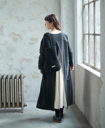 モコモコ素材の黒の大きめボアトートバッグ。可愛くなりすぎてしまう素材感だけれど、黒を選ぶことで落ち着いた印象に。靴、ソックスと小物を黒で統一することで、ワンピースのスリットからチラ見えする白スカートが映えますね。