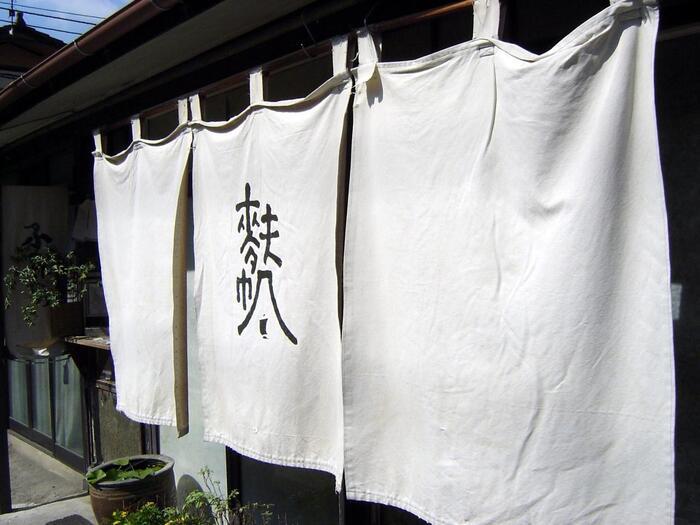 小麦粉から澱粉を取り除いたグルテンを蒸して作られる「生麩」は、鎌倉末期に大陸から伝わった食べもの。動物系のタンパク質を摂取できない禅僧には、貴重なタンパク源となっていました。禅寺が多い京都には、生麩の専門店が数多くありますが、関東では珍しく、禅寺のある鎌倉では、唯一ここ「麩帆」のみです。  【鎌倉駅から徒歩で15分、由比ヶ浜大通りに面した「麩帆」。生麩の販売は、暖簾横の小さな窓口でなされる。土日祭日は、麩まんじゅう目当ての観光客の列が出来る。】