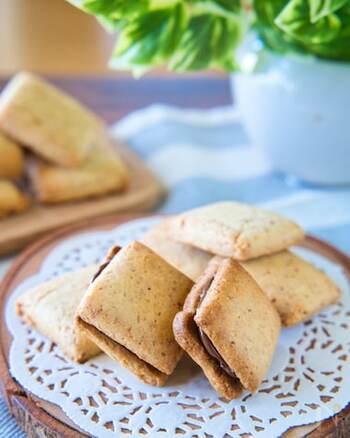 クリームチーズが入ったクッキー生地を焼き上げてから、板チョコをサンドする簡単チョコサンドクッキー。  小さく割った板チョコは、クッキーにはさんでから30秒加熱するだけで、とろりと柔らかく、クッキーに馴染んでくれます。市販のクッキーにチョコをはさみたいときにも使える小技です。覚えておくといいですね。