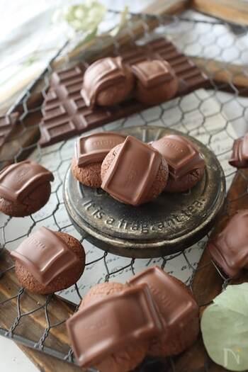 見た目から板チョコの迫力が感じられるココアクッキーです。まんまるに形作ったクッキー生地を焼き上げたら、熱いうちに小さくカットした板チョコをそのままのせるという大胆レシピ。  チョコを溶かしてコーティングするよりも、分厚く、存在感のあるチョコの味を楽しめます。