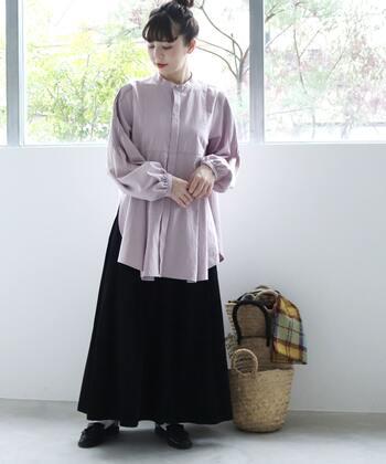 淡いパープルのバンドカラーブラウスに、黒のロングスカートを合わせたコーディネートです。ふわっと広がる女性らしいシルエットのブラウスは、あえて出して今っぽくスタイリング。