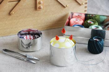 茶筒職人が、ひとつひとつ手づくりしたブリキ缶の中に、手ぬぐいで作った針山が入っている針刺しです。ころんとした形と、ブリキのレトロさが合わさってキュートな雰囲気を演出しています。カラーは、グレー・ブルー・イエローの3色展開です。
