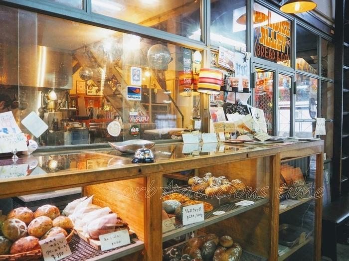 乾物屋や衣料店、焼き鳥店等のテイクアウト中心の店からなる「食品市場」の中でも、朝から盛況なのが市場奥の一角を占める「パラダイス・アレイ」。店主の生まれも育ちも鎌倉で、地元密着、地域に長年愛されて続けてきたベーカリーです。【市場内のエキゾチックで、カオスな雰囲気も魅力的な「PARADISE ALLEYの店頭】