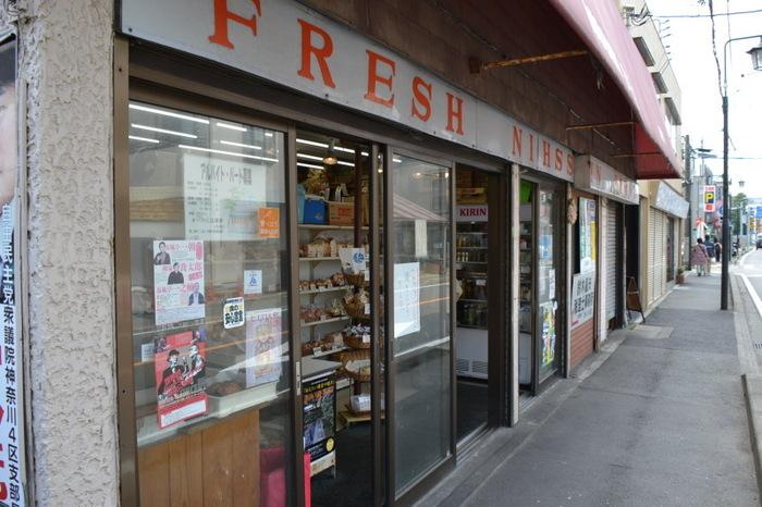 """「北村牛肉店」の交差点斜向いにある「日進堂」は、鎌倉大町の昭和25年頃に創業した老舗店。鎌倉には、新旧様々な洒落たベーカリーがありますが、「日進堂」のような、昭和レトロな佇まいそのままの店も残っています。 この店は、今もなお地域の人々に愛されている""""町のパン屋さん""""。朝6時開店で、年中無休で営業。製造されているパンは、鎌倉の学校給食にも提供されています。"""