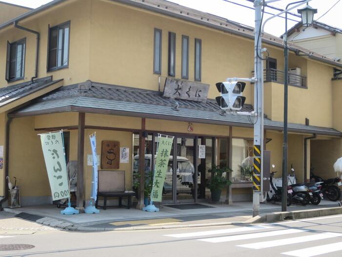 日進堂の並び、小町大路の「大町四ツ角」交差点に一際目立つ建物は、大町のシンボル「御菓子司 大くに」です。1936(昭和11)年の創業以来、厳選した材料を用い、昔ながらに手作りされている、地元で愛されてきた和菓子の老舗です。