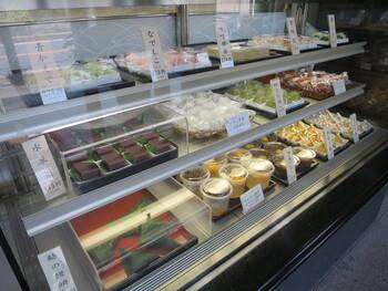 「大くに」で特徴的なのが、販売されている菓子の種類が実に豊富であること。 長く伸びる店のショーケースには、季節を映した上生菓子や、柏餅や麩まんじゅう等、様々な種類の生和菓子が常時並べられ、他に、棹物、干菓子、焼き菓子、赤飯といった商品も用意され、寺院が多く、茶の湯も盛んな古都「鎌倉」ならではのラインナップです。  【麩まんじゅうやみつ豆の他、上生菓子が並ぶショーケースの一角。店内は、清潔で明るく広やか。】