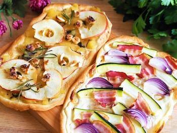 ドイツ南西部からフランス北東部にかけて広がる、アルザス地方で生まれたフラムクーヘン。パン生地を伸ばして、その上にサワークリーム、玉ねぎ、ベーコンなどを乗せ、フラム(flamm)=炎で焼き上げる料理です。上にのせる具材によって印象が全く違ってくるので、アレンジはあなた次第。例えばこちらのレシピでは、紫玉ねぎやズッキーニを使って色鮮やかに仕上げています。パプリカ、ルッコラ、トマト、ナスなども合いそうですね。