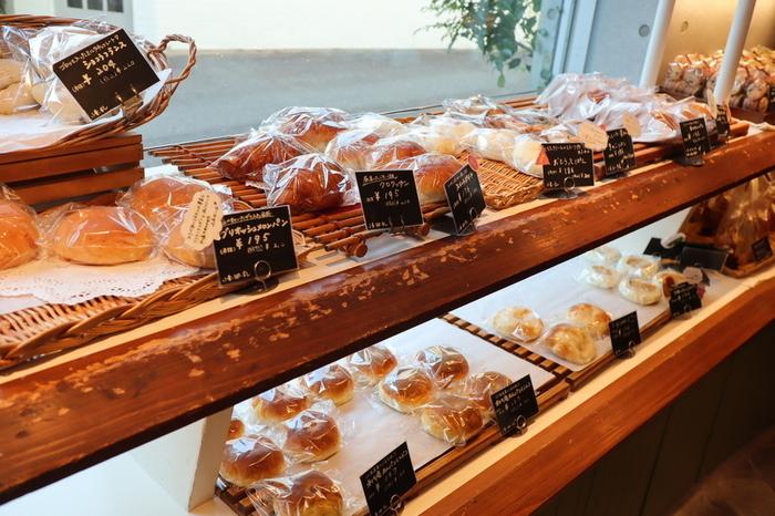 """「鎌倉利々庵」の特徴は、何をおいても、店頭に並べられる商品が実に種類豊富であること。小規模、少品種の商業形態が、潮流となりつつある昨今において、この店はそういった流れとは対極的。""""毎日約100種類。お客様が100回、笑顔になれるように。""""と掲げるように、毎日様々な種類の手作りのオリジナルパンが店内に並べられています。  食パンやバゲット、カンパーニュやクロワッサンといった食事系のシンプルなパンだけでも十数種。他に、カレーパンやサンドイッチといった惣菜パンや調理パン、スコーンやラスク等の焼き菓子系も種類豊富です。その中でも充実しているのが、菓子パン類。あんぱんやコルネ、メロンパンやデニッシュ、ミルクフランス等など、色とりどりです。  またカレーパンやスコーンと一口に言っても、それぞれ異なる味わいのものが、それぞれ数種用意、実にバラエティ豊かです。【あんぱんやクロワッサン等が並ぶ店内陳列棚の一角。】"""
