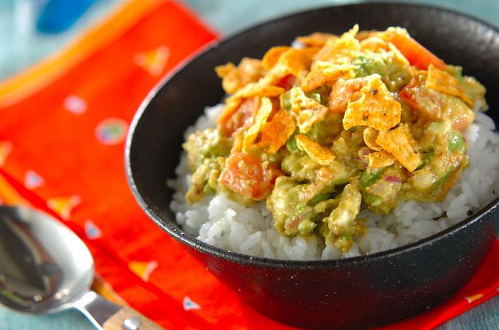 アボカドや紫玉ねぎ、タコスシーズニングなどで作るワカモレをご飯にのせたレシピです。野菜を切っておけば、あとは混ぜてのせるだけなのでとっても簡単。仕上げにトルティーヤチップを散らしてアクセントにしましょう。