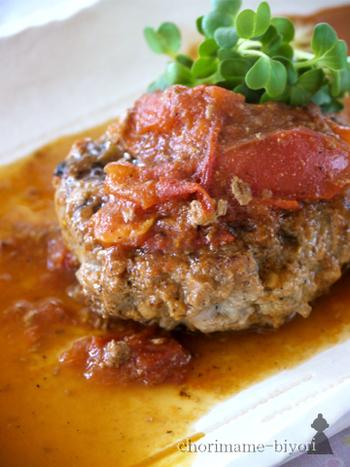 トマト醤油ソースでいただくハンバーグのレシピ。牛ももブロック肉を粗びきした牛100%のハンバーグなので、和風ベースなのに濃厚な味わいを堪能できます。 牛肉のうま味をリーズナブルに楽しみたい時におすすめのレシピです。