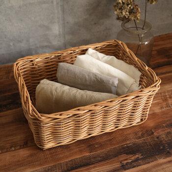 風通しがよいカゴ・バスケットは、キッチン収納にも役立つアイテムです。こちらのように畳んだクロスを入れたり、普段あまり使わない食器やお弁当グッズをまとめたりと、アイディア次第で使い方は無限大。天然素材ならではのナチュラルな風合いが可愛いので、オープンタイプの食器棚など目につく場所に置いても様になります。