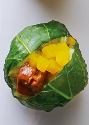 塩ゆでした小松菜の葉できれいに包んだおにぎり。ご飯には刻んだ小松菜とたくあんを混ぜていて、味も食感も楽しめます。トッピングに缶詰のやきとりとたくあんを。色鮮やかで素敵な見た目なのに手軽な具材で作れるレシピです。