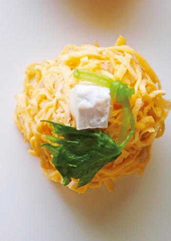 カマンベールとカツオ、醤油を混ぜたおにぎりに卵をトッピングした斬新なおにぎり。千切りにした薄焼き卵は、ラップを使うことできれいに巻きつけることができます。三つ葉のアクセントが、香りと見た目のポイントに。