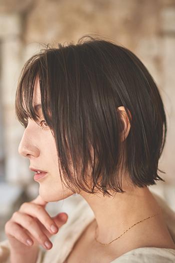 重くもたつかない、ラインが綺麗なボブ。イルミナのカラー剤で落ち着いたアッシュ系に染め上げました。寒色系のカラーは肌を白く見せてくれるので、女性らしさをより際立ててくれます。スタイリングは、へアオイルと軟らかいヘアワックスを1:1の割合で混ぜたものを髪の毛全体になじませて前髪をセンターパートでジグザグにとってシースルーバングを作ります。サイドヘアとバックヘアは柔らかく外にハネさせると、今っぽいスタイリングに仕上がります。