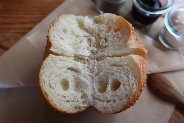 「なみまち」のベーグルの生地は、北海道産の小麦「はるゆたか」のみを贅沢に用いています。加えるのは、ホシノ天然酵母、沖縄の塩シママース、蜂蜜と実にシンプル。バター、牛乳、卵、砂糖も一切使わないので、体に優しく、低カロリーです。  「なみまちベーグル」は、むっちりとして噛み応えがある通常のベーグルと異なります。外皮はカリッとして、中がふんわりとしてもっちり。噛みしめる程に、小麦本来の旨味、国産小麦特有の甘み、天然酵母ならではの風味が、口の中で膨らんでいきます。  お勧めは『プレーン』。当店の特徴が良く出た逸品です。テイクアウトして家で食べる時は、軽く温めてから頂きましょう。香ばしく、生地の表面と中味の異なる食味が楽しめます。材料がシンプルなので、そのままでも、ディップを付けても、サンドイッチにしても、美味しく頂けます。【色良く、艶良く、気泡も見事な『プレーン』】